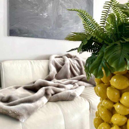 Plaid aus Webpelz von der Marke Carma und extravagante Vase mit Zitronen von Van Roon Living