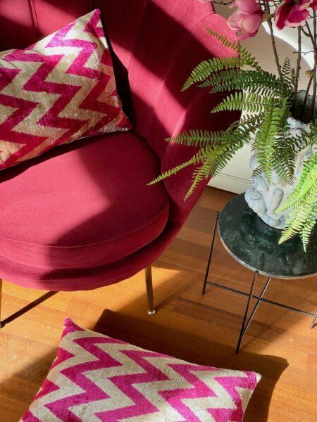 Dekoration Zuhause, gemütlicher Loungesessel und Kissen aus Seidensamt